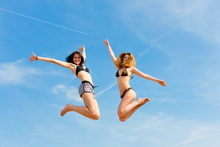 Two happy women jumping high in summer with fun with the blue sky in the background photo