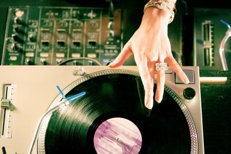 giradisco: DJ femminile presso il giradischi in un club, con mixer e vecchia scuola record player