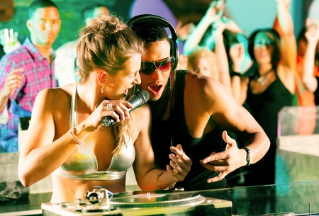 Two DJs - male and female, black and white - in a club at the turntable, in the background a crowd of their fans cheering and dancing Stock Photo - 9860941