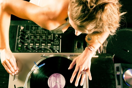 turntable: Female DJ at the turntable in a club, with mixer and old school record player    Stock Photo
