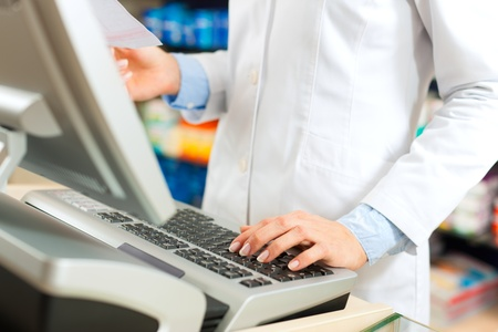 cashpoint: Female pharmacist standing at the cashier in pharmacy, only the torso to be seen