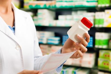 recetas medicas: Farmac�utico femenina-s�lo las manos para verse - permanente en farmacia con productos farmac�uticos Foto de archivo