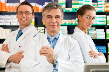 farmacia: Farmacista con la sua posizione di squadra in farmacia o in farmacia di fronte scaffali con prodotti farmaceutici