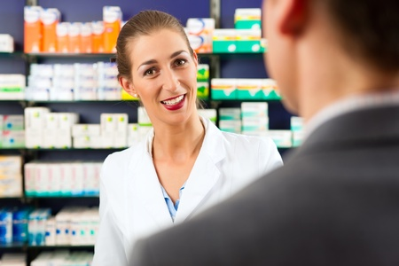 Female pharmacist consulting a customer in pharmacy photo