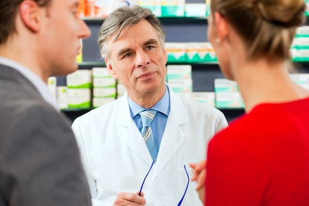 Pharmacist is consulting customers in his pharmacy - a man and a woman