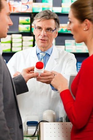 pharmacist: Pharmacist with customers in pharmacy, he is holding a bottle with pharmaceuticals in his hand