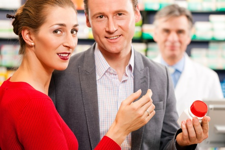 Pharmacist in pharmacy; in front customers - man and woman - he is holding a bottle with pharmaceuticals in his hand Stok Fotoğraf