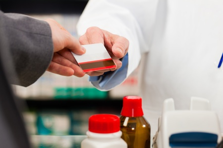 Pharmacist with customer in pharmacy; the customer pays with credit card; from both only the hands are seen Stok Fotoğraf