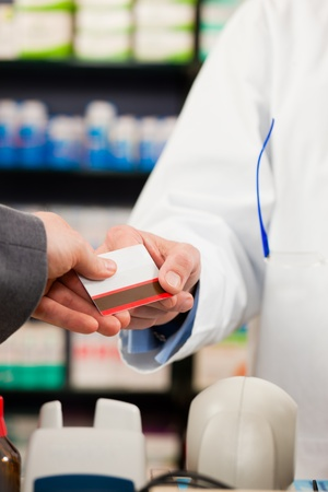 health reform: Pharmacist with customer in pharmacy; the customer pays with credit card; from both only the hands are seen Stock Photo