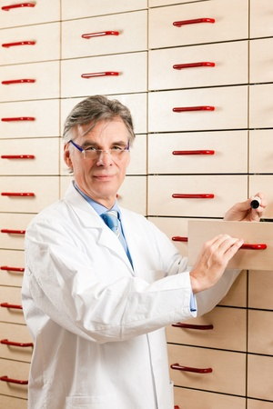Pharmacist in front of medicine chest is looking for some medicine photo