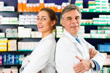 Two Pharmacists standing in pharmacy or drugstore in front of shelves with pharmaceuticals Stok Fotoğraf