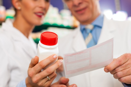 drug store: Two pharmacists with pharmaceuticals in hand consulting each other in a pharmacy Stock Photo