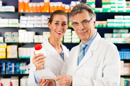 pharmacy store: Two pharmacists with pharmaceuticals in hand consulting each other in a pharmacy Stock Photo