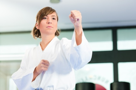fighting arts: Woman in martial art training in a gym, she is wearing a black belt