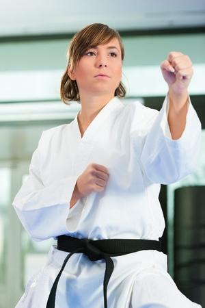 arte marcial: Mujer en el arte marcial de entrenamiento en un gimnasio, ella lleva un cintur�n negro. Foto de archivo