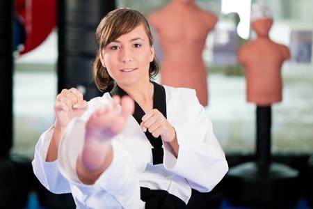 artes marciales: Mujer en el arte marcial de entrenamiento en un gimnasio, ella está haciendo una patada frontal de taekwondo