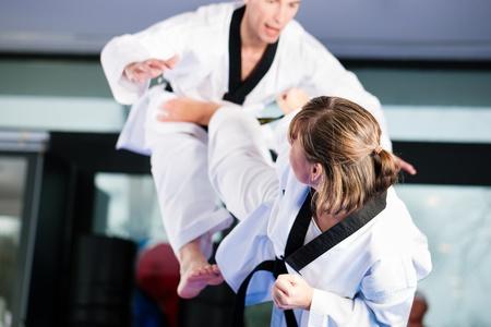 artes marciales: Personas en un gimnasio de artes marciales de formaci�n ejercicio de Taekwondo, ambos tienen un cintur�n negro. Foto de archivo