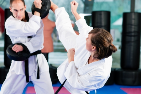 People in a gym in martial arts training exercising Taekwondo, both have a black belt photo