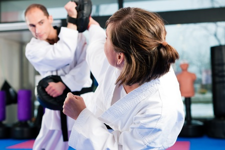 martial arts: People in a gym in martial arts training exercising Taekwondo, both have a black belt