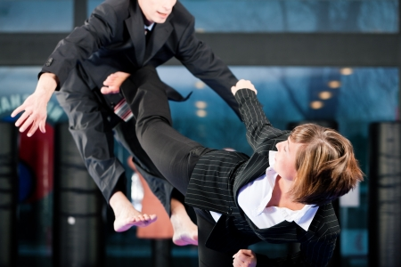martial arts woman: Business concept - People in a gym in martial arts training exercising Taekwondo, both wearing suits