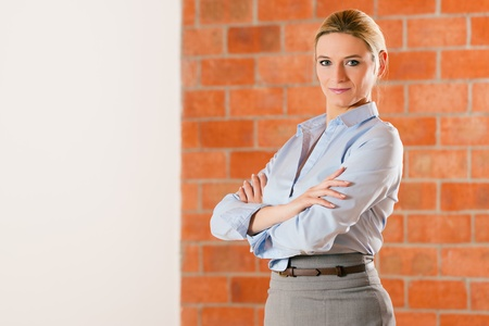 accommodation broker: Woman standing with folded arms in an empty apartment