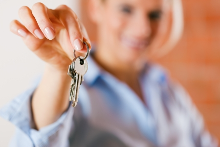 accommodation broker: Woman is giving the keys to an apartment to some clients focus on the keys