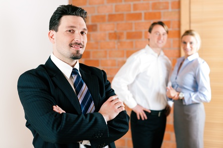 property agent: Businessperson in an empty apartment with some clients looking for real estate Stock Photo