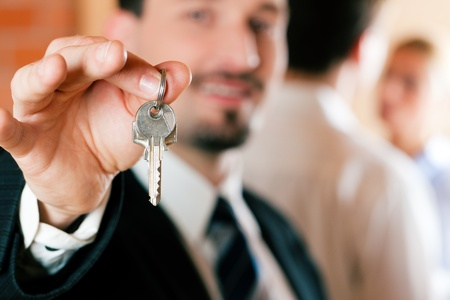 Young couple buying or renting a home or apartment, they are meeting the owner or real estate broker who has the keys; FOCUS on keys Stock Photo - 10021149