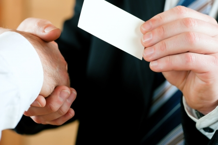 give hand: Businessmen having handshake, one handing business card over; only hands to be seen
