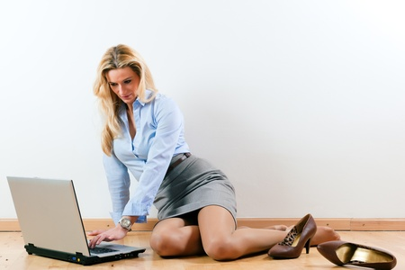 closing time: Business woman working at home with her laptop on the floor