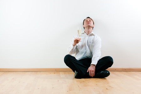Man sitting cross-legged on the wooden floor of his apartment photo