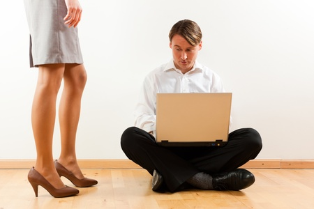 Businesspeople at home; he is sitting with laptop on the floor photo