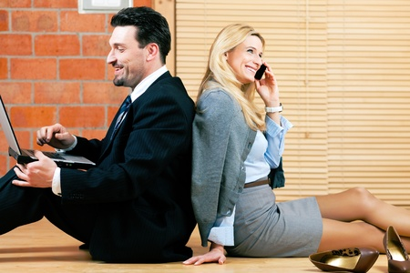 Businesswoman and businessman working at home sitting on the floor photo