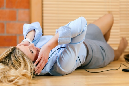 Business woman listening music or a language course at home lying relaxed on the floor Stock Photo