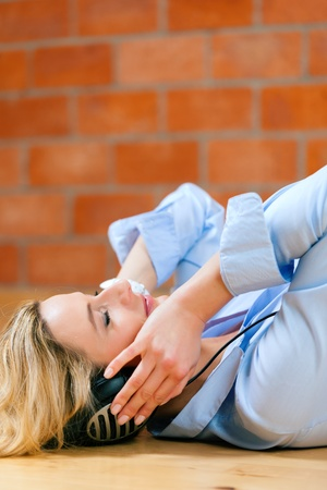 Business woman listening music or a language course at home lying relaxed on the floor photo