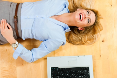 Businesswoman is lying on the floor at home relaxing, a laptop beside her photo
