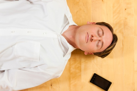 Man lying with closed eyes on the floor at home, a telephone beside him photo