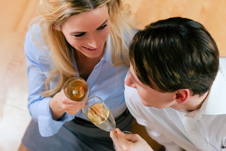 Business Couple - man and woman - at home with champagne sitting on the wooden floor clinking glasses photo