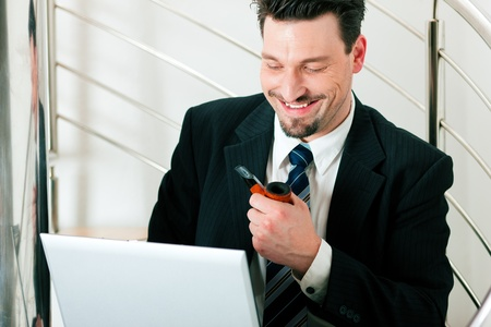 Businessman working at home with his laptop sitting on the stairs in his apartment Stock Photo - 10021630