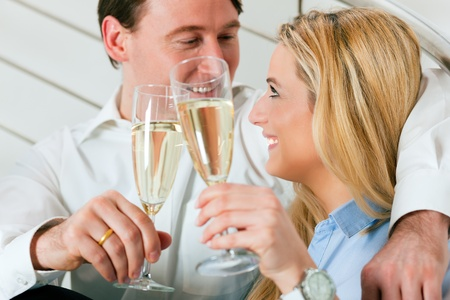 Business Couple - man and woman - at home with champagne sitting on stairs in their apartment photo