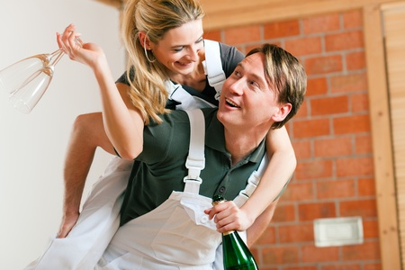 tenant: Young couple moving in new flat doing renovation and painting, celebrating their new home with sparkling wine Stock Photo