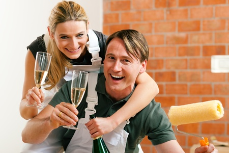 tenant: Young couple moving in new flat doing renovation and painting, celebrating their new home with sparkling wine