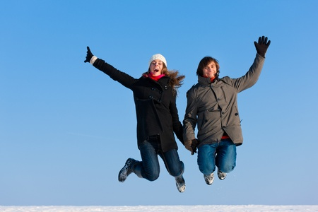 Couple - man and woman - jumping high on a winter day photo