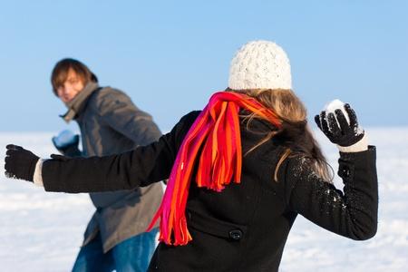 bolas de nieve: Pareja - hombre y una mujer - que tiene una bola de nieve en invierno Foto de archivo