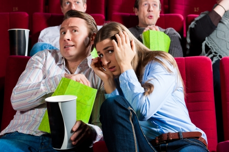Couple in cinema watching a movie; it seems to be a horror movie photo