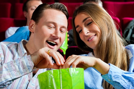 theater audience: Couple in cinema watching a movie; they eating popcorn