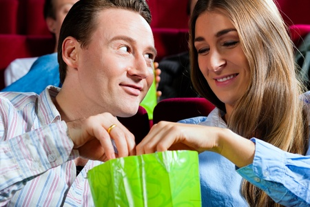 Couple in cinema watching a movie; they eating popcorn Stock Photo - 10020514