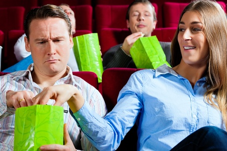 Couple in cinema watching a movie; they eating popcorn Stock Photo - 10020513