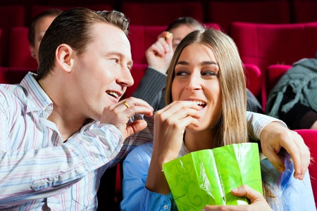 they are watching: Couple in cinema watching a movie; they eating popcorn