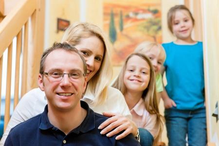 trois enfants: Famille heureuse avec trois enfants � la maison sur l'escalier Banque d'images